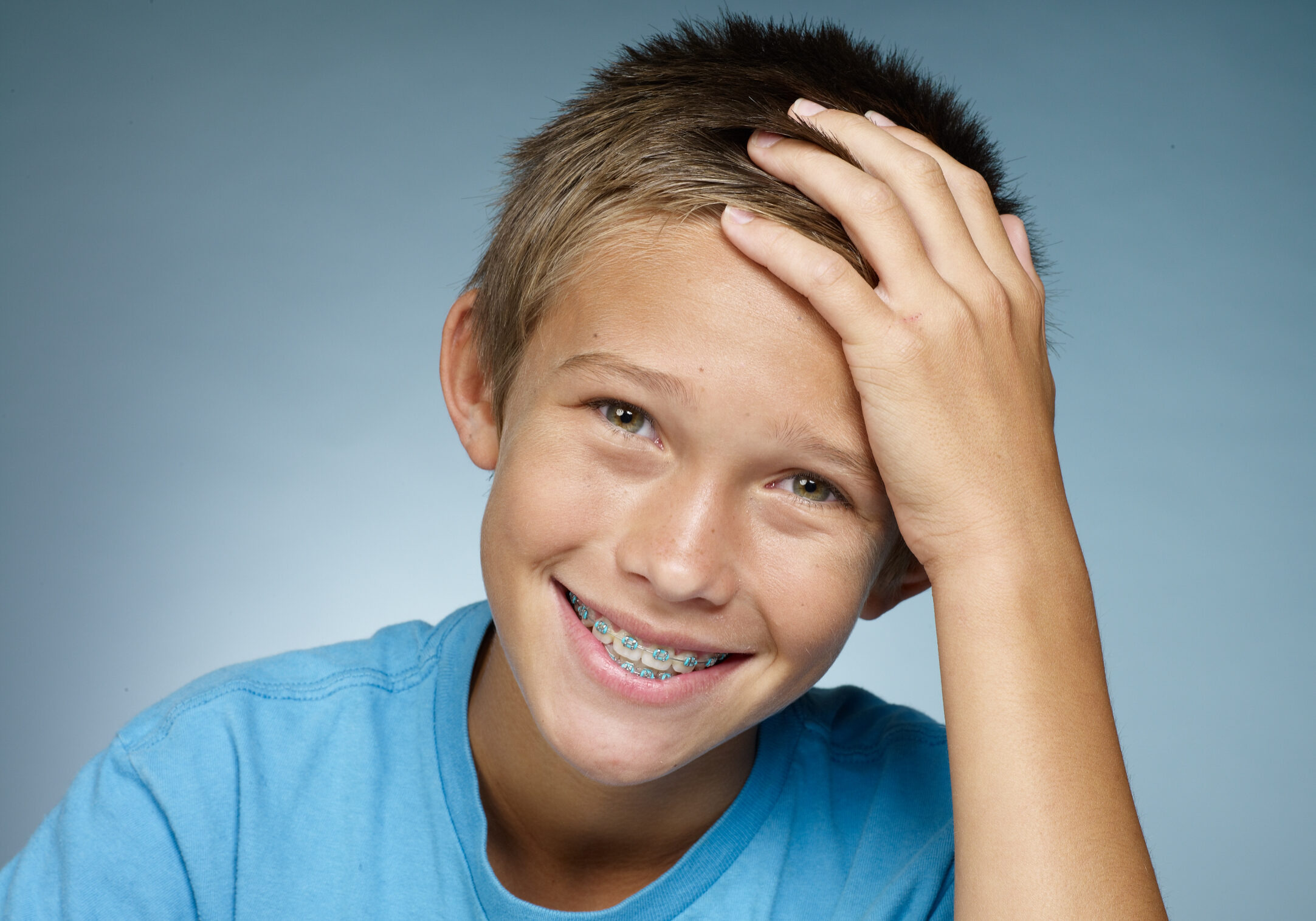 Preteen with braces, smiling with his hand on his forehead