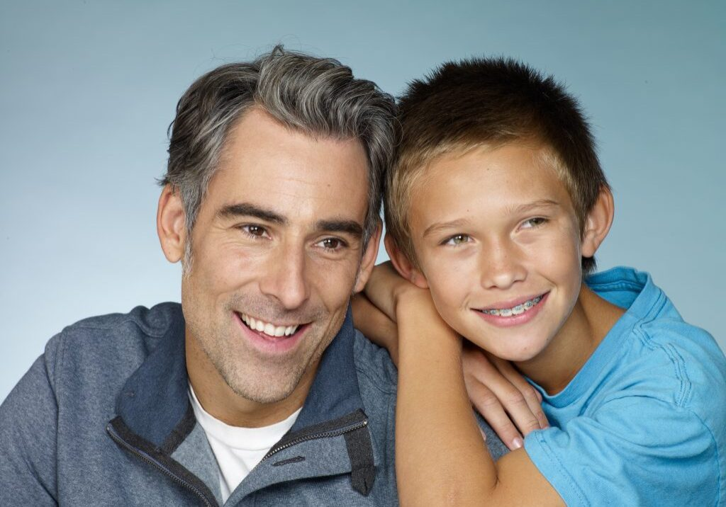 father and son, son with braces, both smiling